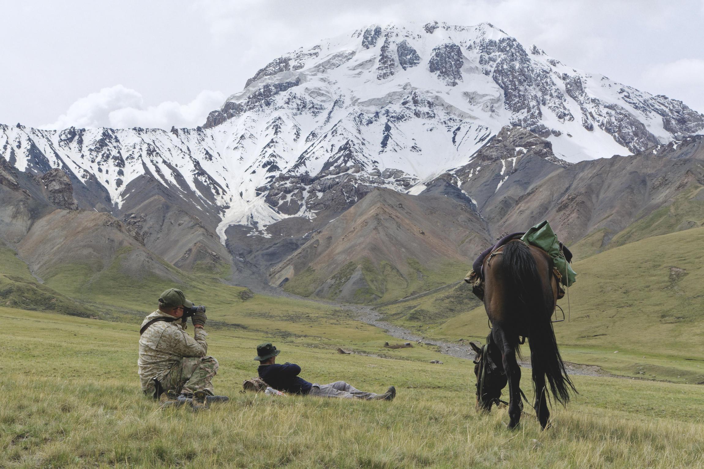 Hommes et cheval devant un massif enneigé Kaindy Kirghizstan