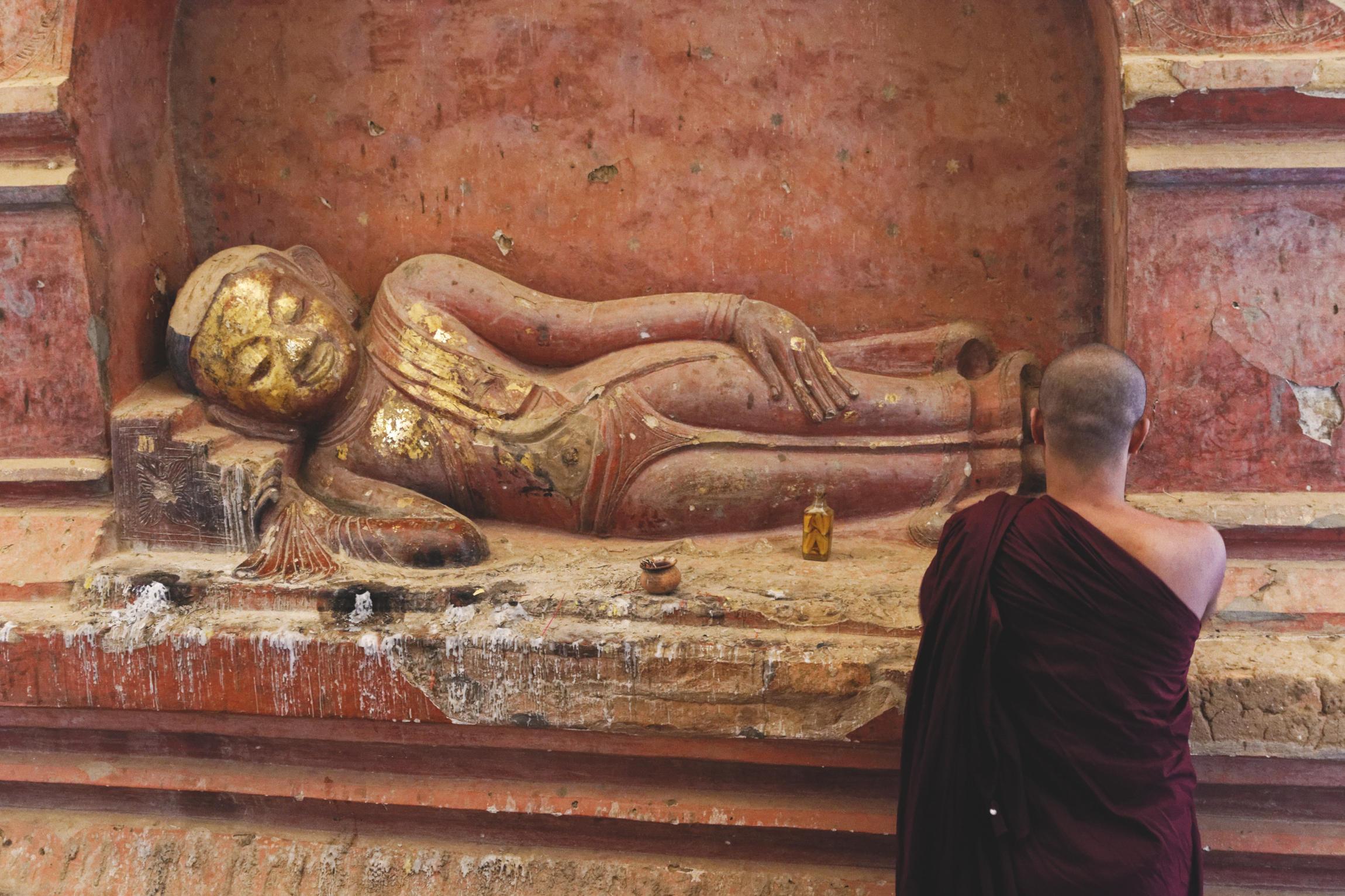 Bonze en train de prier devant une sculpture de Bouddha Bagan